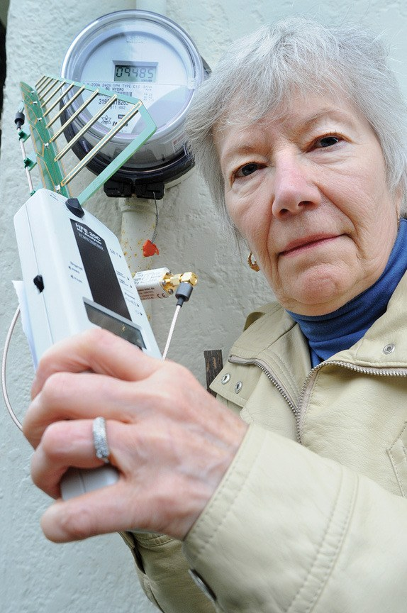Sharon Noble holds a high-frequency analyzer next to one of B.C. Hydro's electromechanical meters. This meter